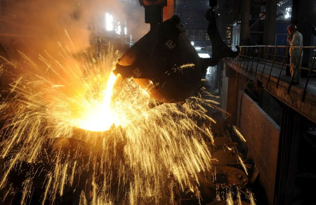 FILE PHOTO: An employee monitors molten iron being poured into a container at a steel plant in Hefei, Anhui province