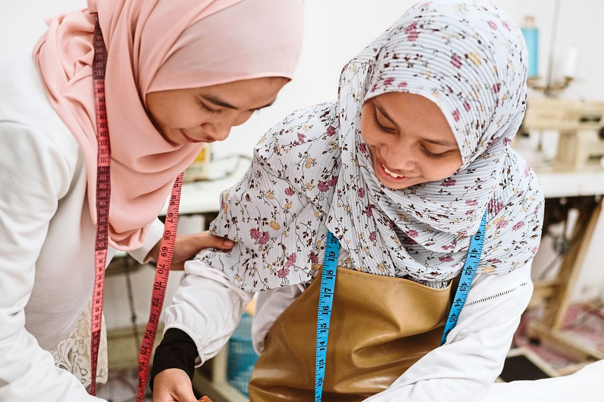Nursyafiqah (left) has learned how to sew and is earning a steady income.