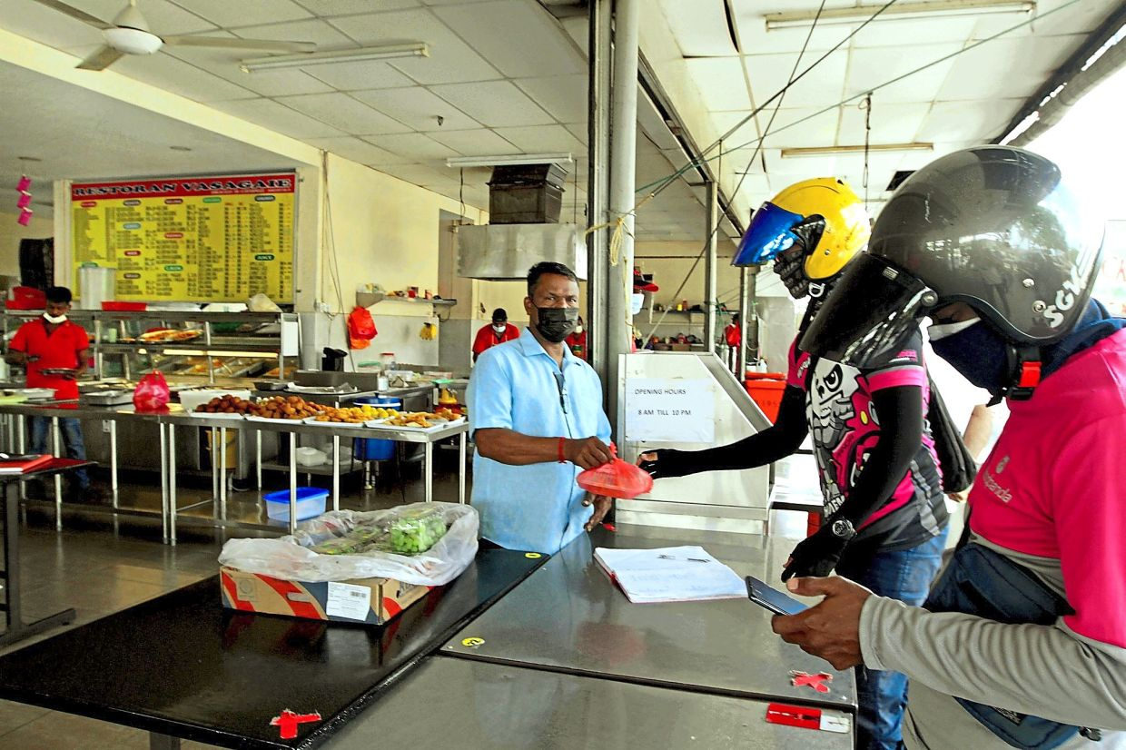 Delivery riders (right) collecting food orders from Kanna at his restaurant in Klang.