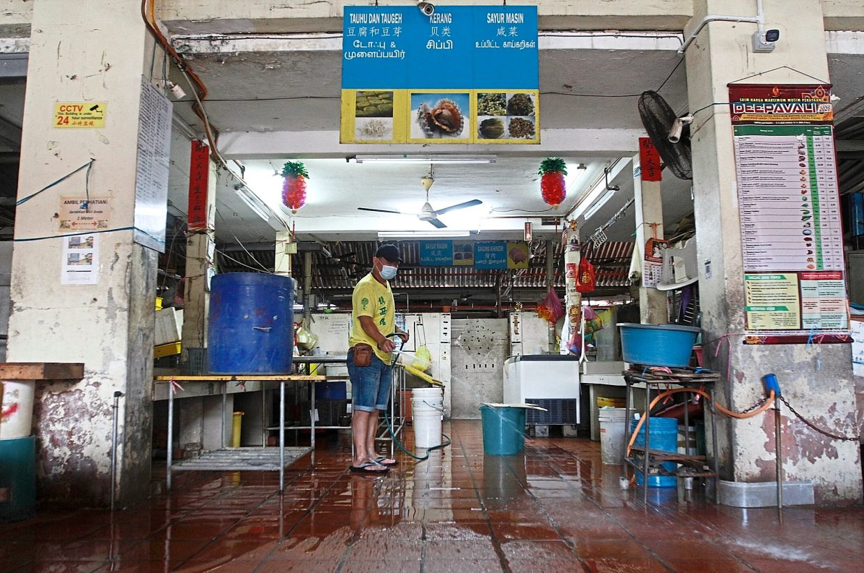 Fishball seller Thor Eng Tatt, 45, cleaning his stall after the reopening of the Jelutong Market in Penang.