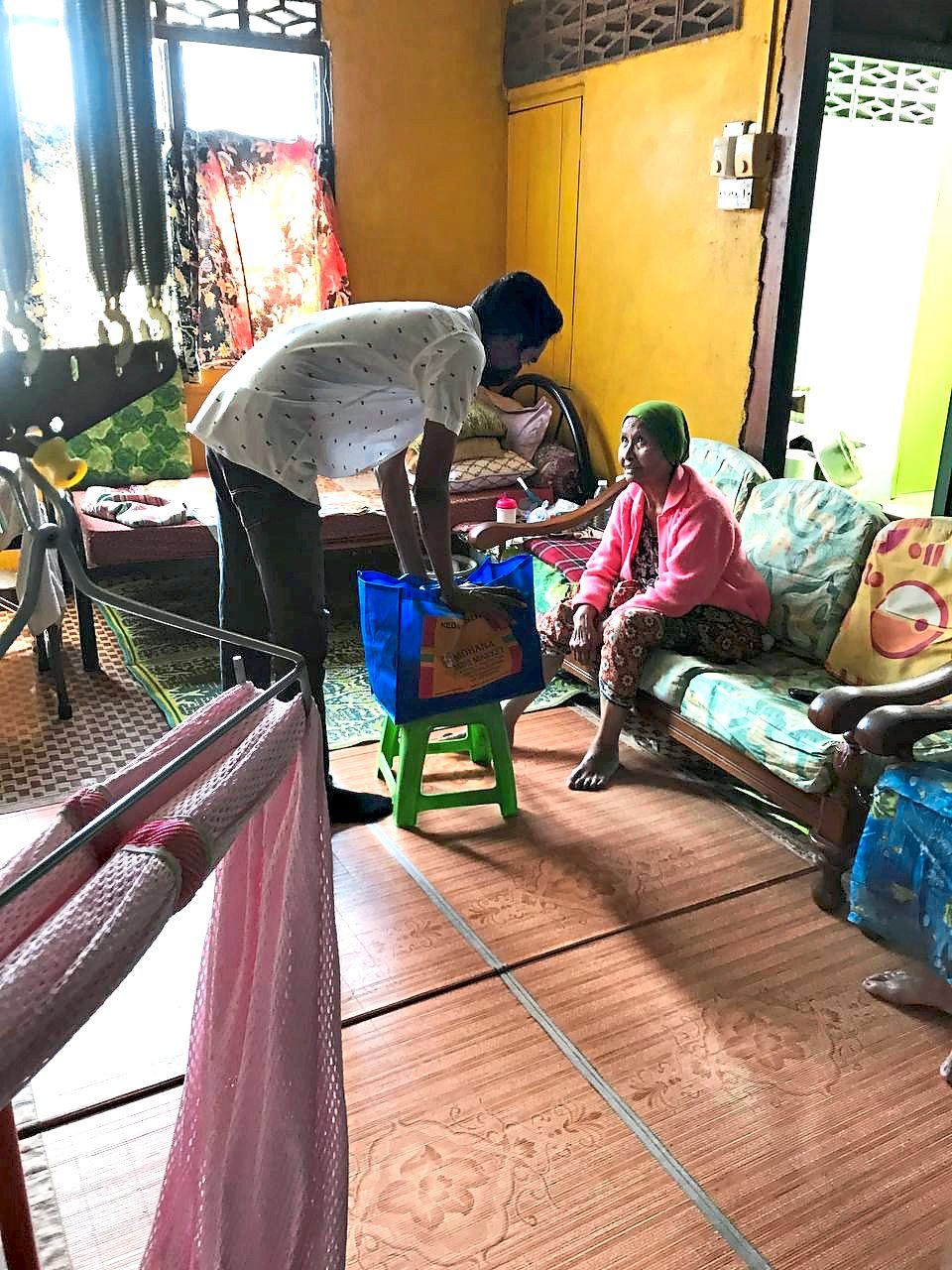Praviin (left) delivering food supplies to a needy family in Mantin, Negri Sembilan in February.