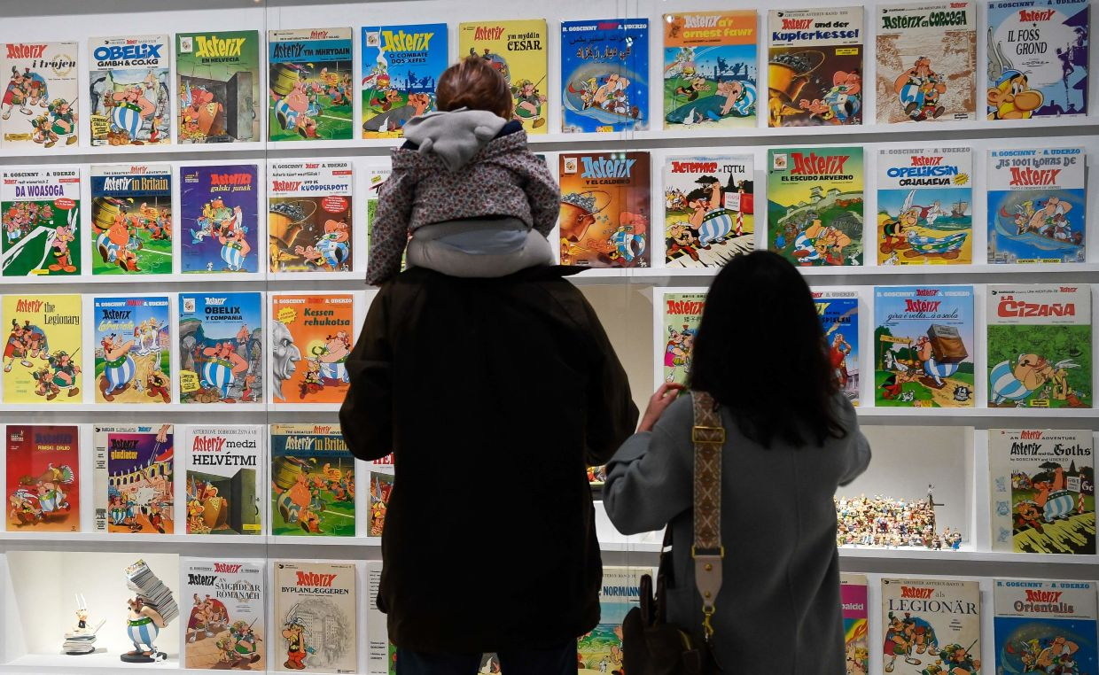 Visitors look at comics displayed during the exhibition 'Uderzo, Like A Magic Potion' at the Maillol Museum in Paris. Photo: AFP
