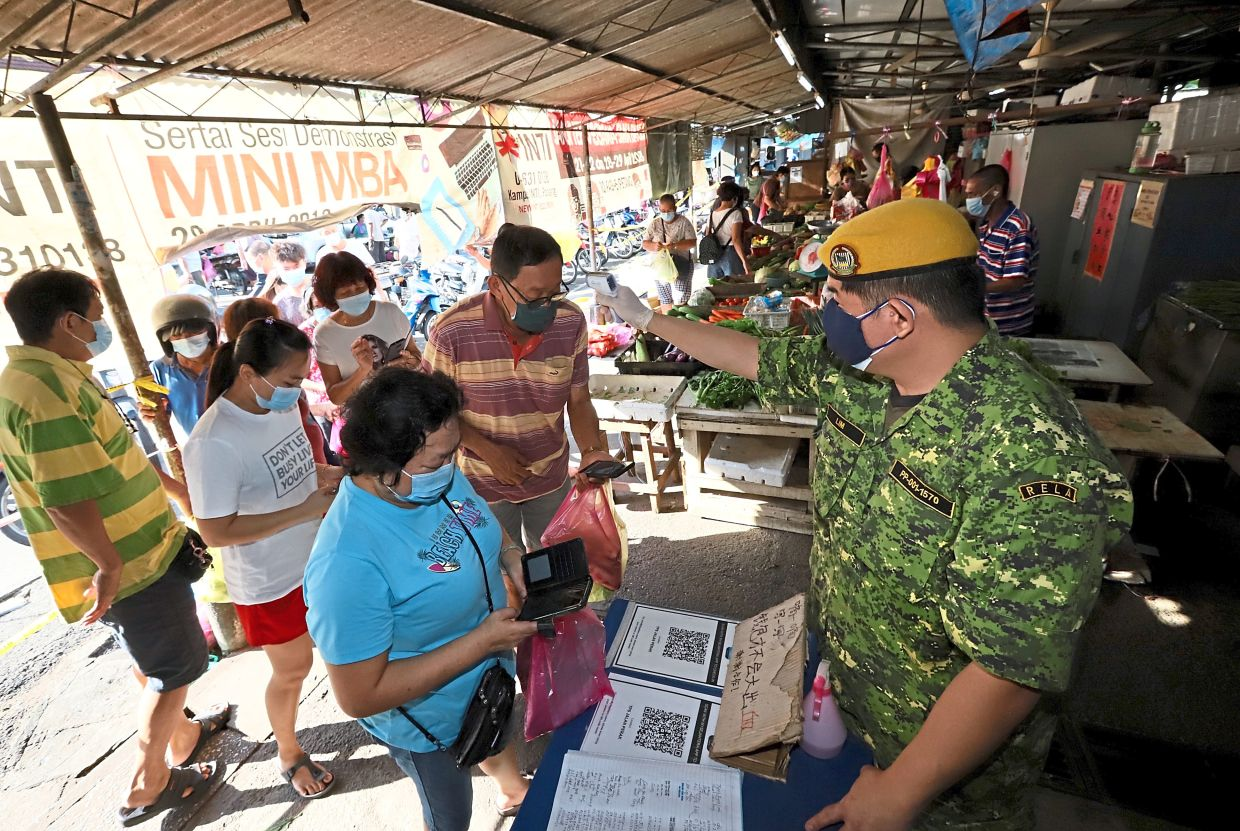 A Rela member scanning the temperature of a market-goer at the entrance of the Perak Road Market.