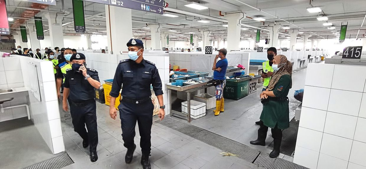 Sentul  district policemen making their rounds at the new market complex on the first day of operations.