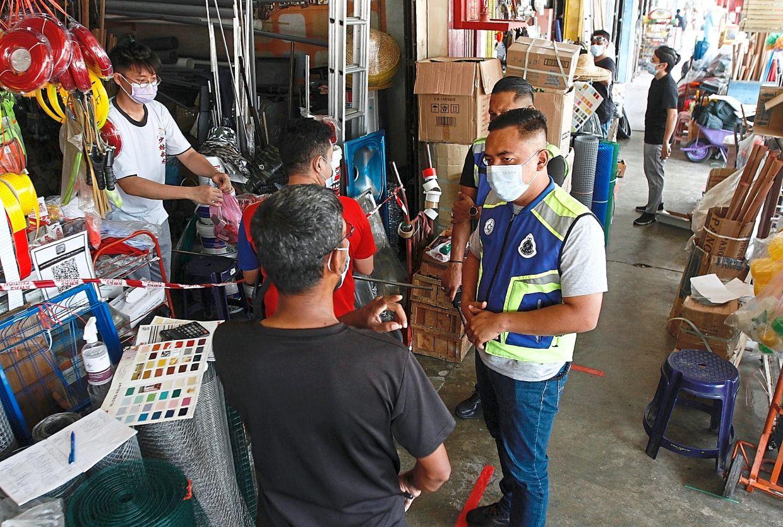 A police team screening customers at a hardware store in Tasek Gelugor, Penang.