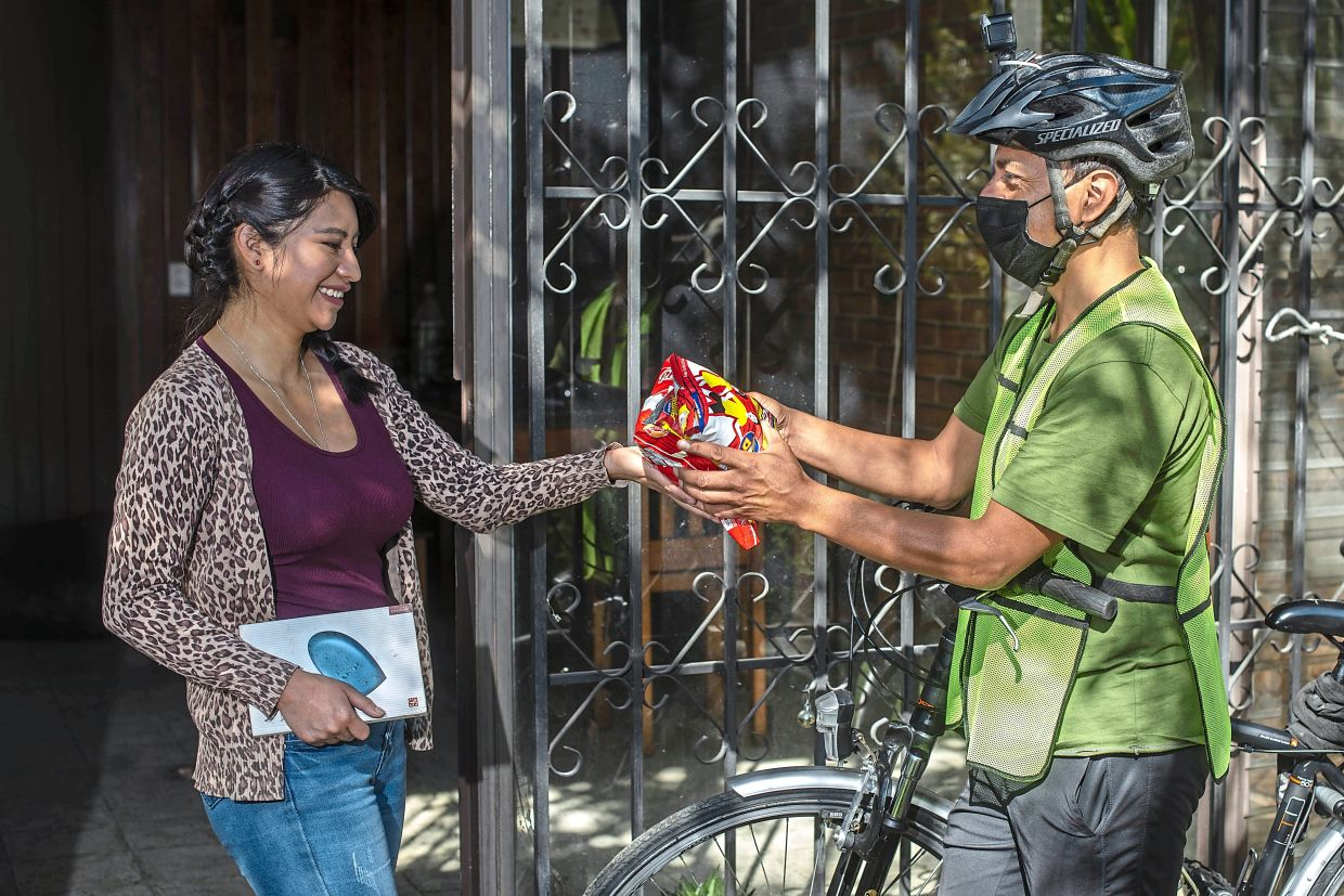 Ana Castillo (left) trades four pounds (1.8kg) of a cereal mix for a sociology book delivered by Diaz in Quetzaltenango in January. Photo: Henning Sac/AP