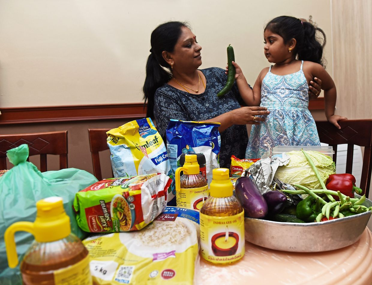 Santhi with her granddaughter Rhyaa  sorting out the food  and fresh vegetables that she has stocked up.