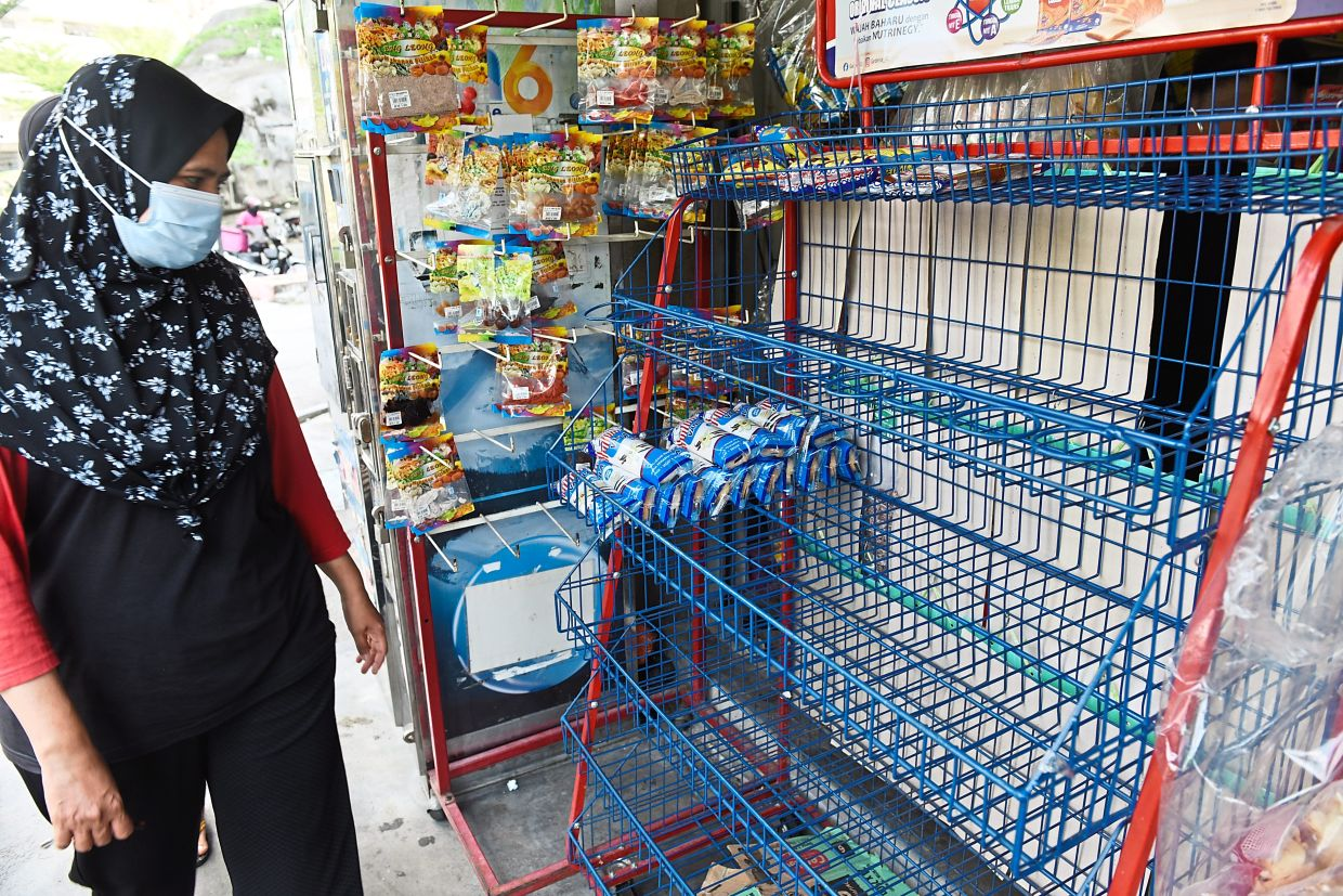 A woman staring at the near empty shelf usually filled with buns and bread at a mini market within the area marked for enhanced MCO in Bayan Lepas, Penang.