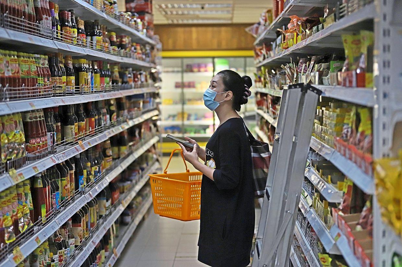 A customer choosing sauces at a supermarket.