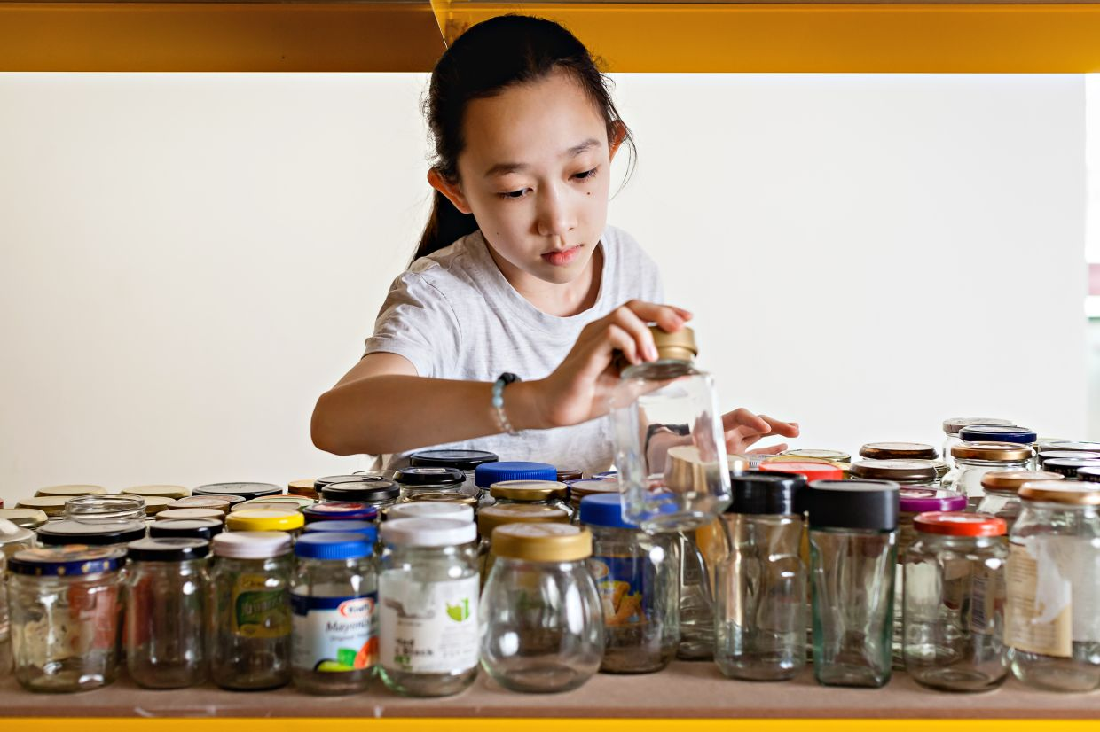 Lau has a little helper in the kitchen in her daughter Hayley, who helps sort out the recyclable glass jars for snacks.  Photo: Asther Lau