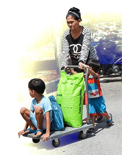 Children accompanying a woman as she pushes a trolley loaded with household essentials near the Sri Bayu Apartments.