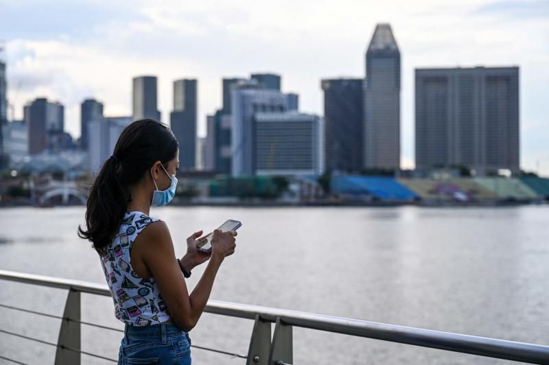 An advertising executive who wanted to be known as Erica checking her mobile phone along the Marina Bay promenade in Singapore. Erica is among a growing number of women travelling overseas to get their eggs frozen, as people in the work-obsessed city-state increasingly delay having children. - AFP