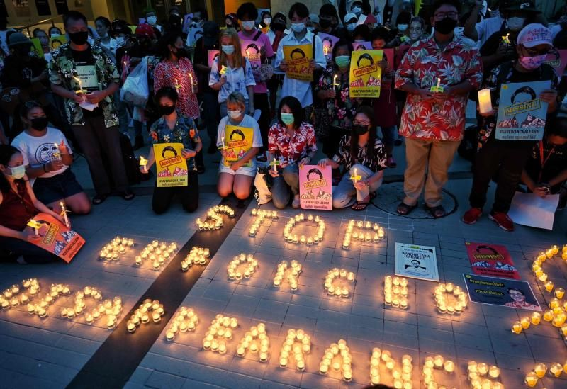 Pro-democracy protesters and Sitanun Satsaksit (centre) sister of Thai activist Wanchalearm Satsaksit, who went missing in Cambodia in 2020, commemorates the first anniversary of his enforced disappearance with a candlelight vigil in Bangkok on June 4, 2021. - AFP