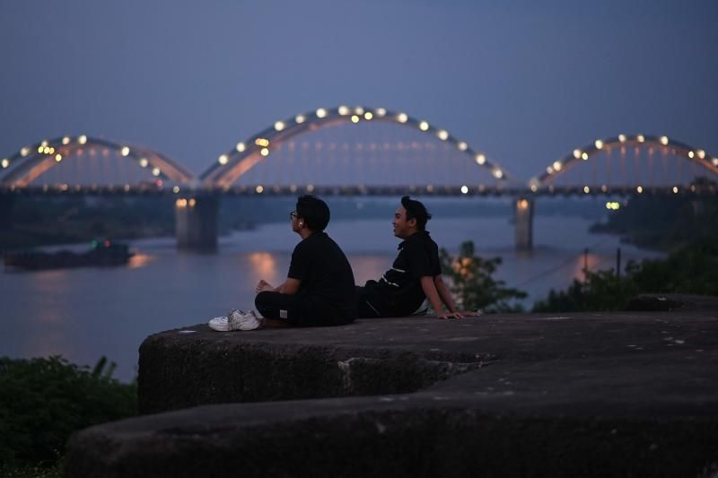 Young men relaxing before the Dong Tru bridge along the banks of the Red river at dusk in Hanoi on June 4, 2021. - AFP