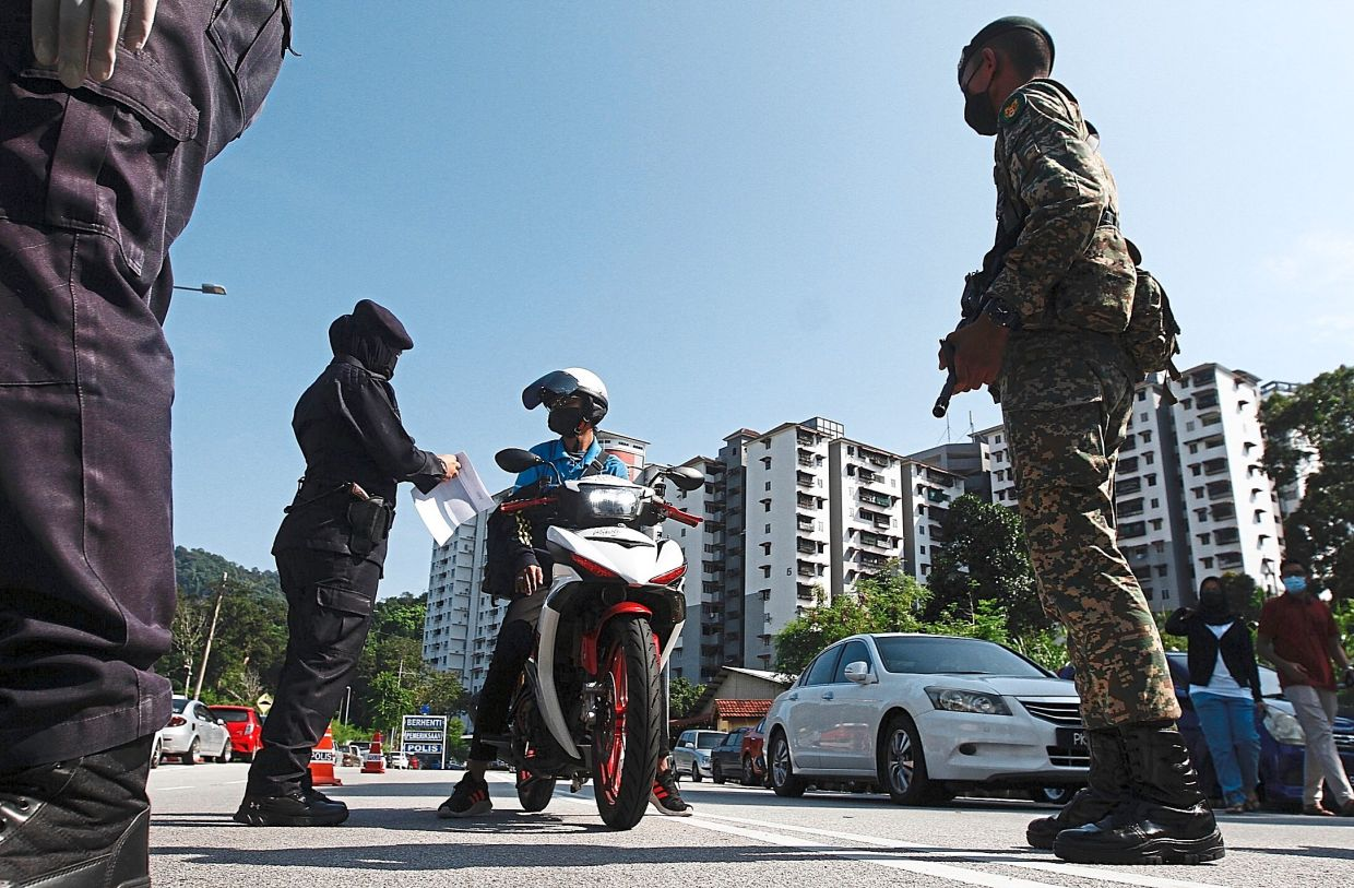Police personnel questioning a motorcyclist at a police roadblock set up near Sri Bayu in Bayan Lepas.