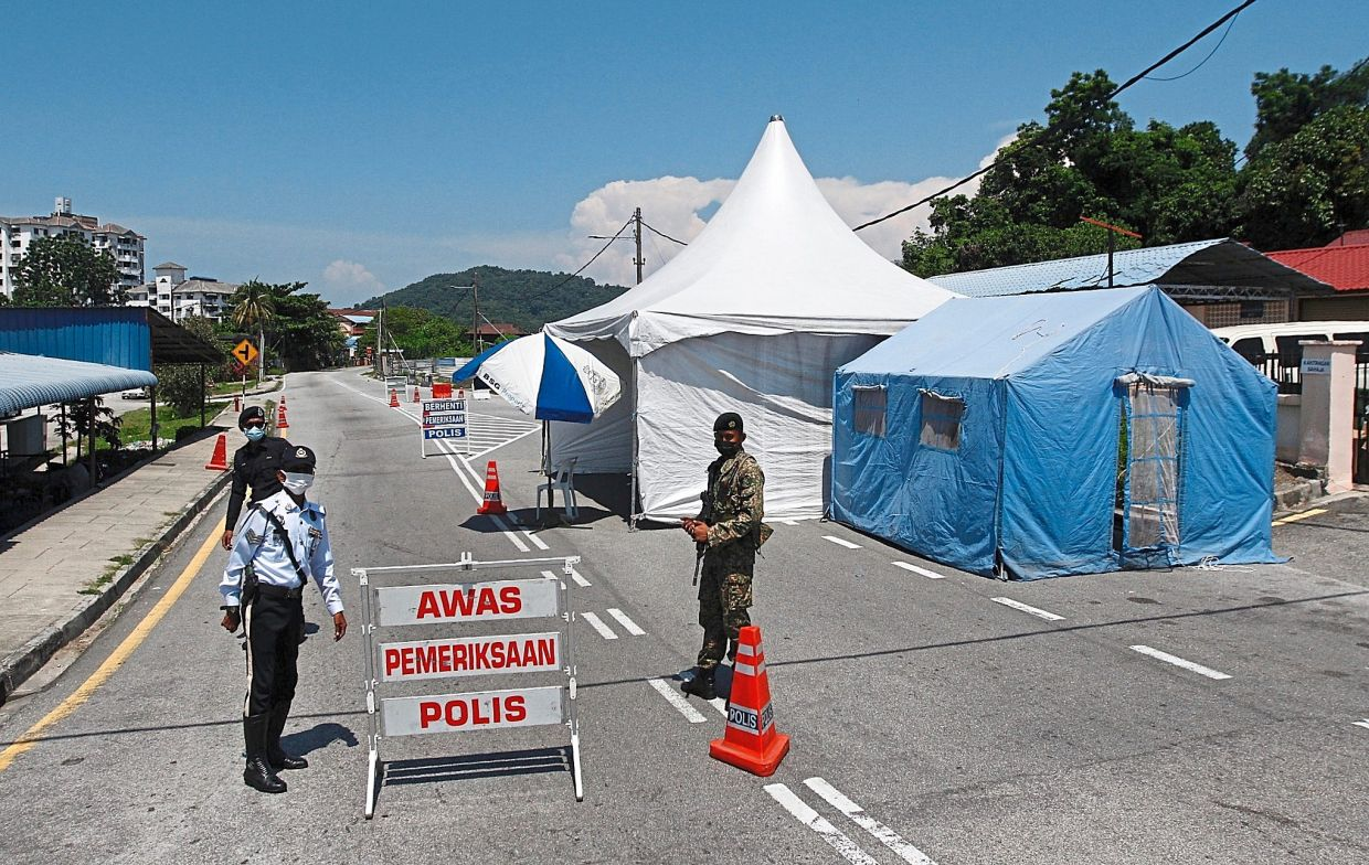 Police and army personnel manning a roadblock in Sungai Ara to restrict movement of people near the enhanced MCO area in Bayan Lepas, Penang.