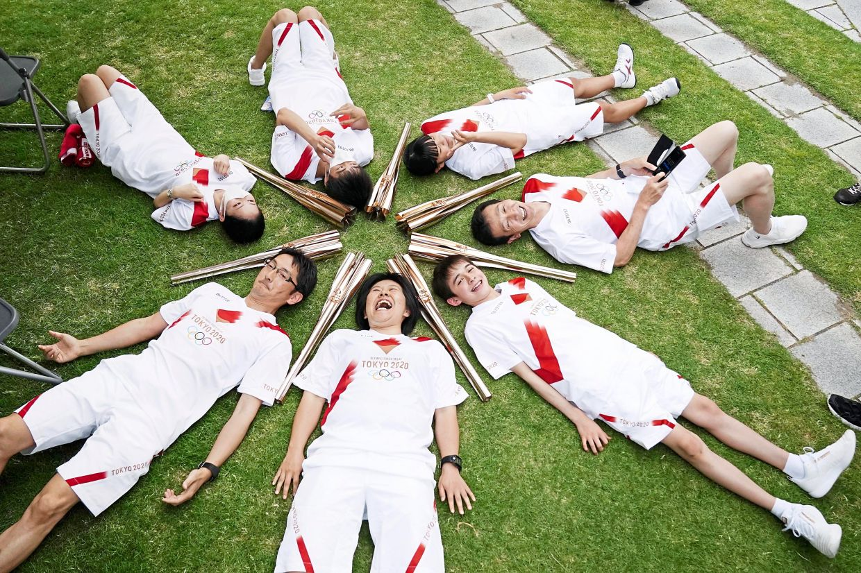 Tokyo Olympic torch relay participants lie in a circle during an alternative event for the torch relay, amid the Covid-19 outbreak in Toyama, Japan. — Reuters
