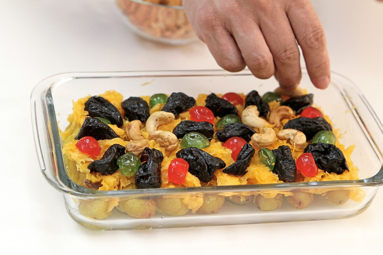 The top most layer comprises dried prunes,  cherries and fried cashew nuts as garnish.