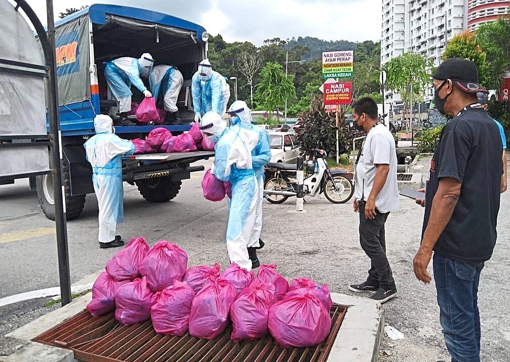 Volunteers coming forward to help Civil Defence Force personnel who unloaded food items from a truck for distribution among residents within the 13 localities in Bayan Lepas, Penang. — K.T. GOH and ZHAFARAN NASIB/The Star