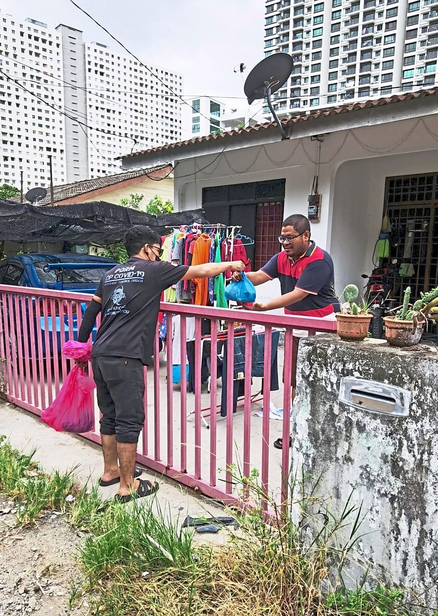 A Bayan Lepas MPKK member handing out food aid and fresh chicken to an affected resident in one of the 13 localities under enhanced MCO in the area.