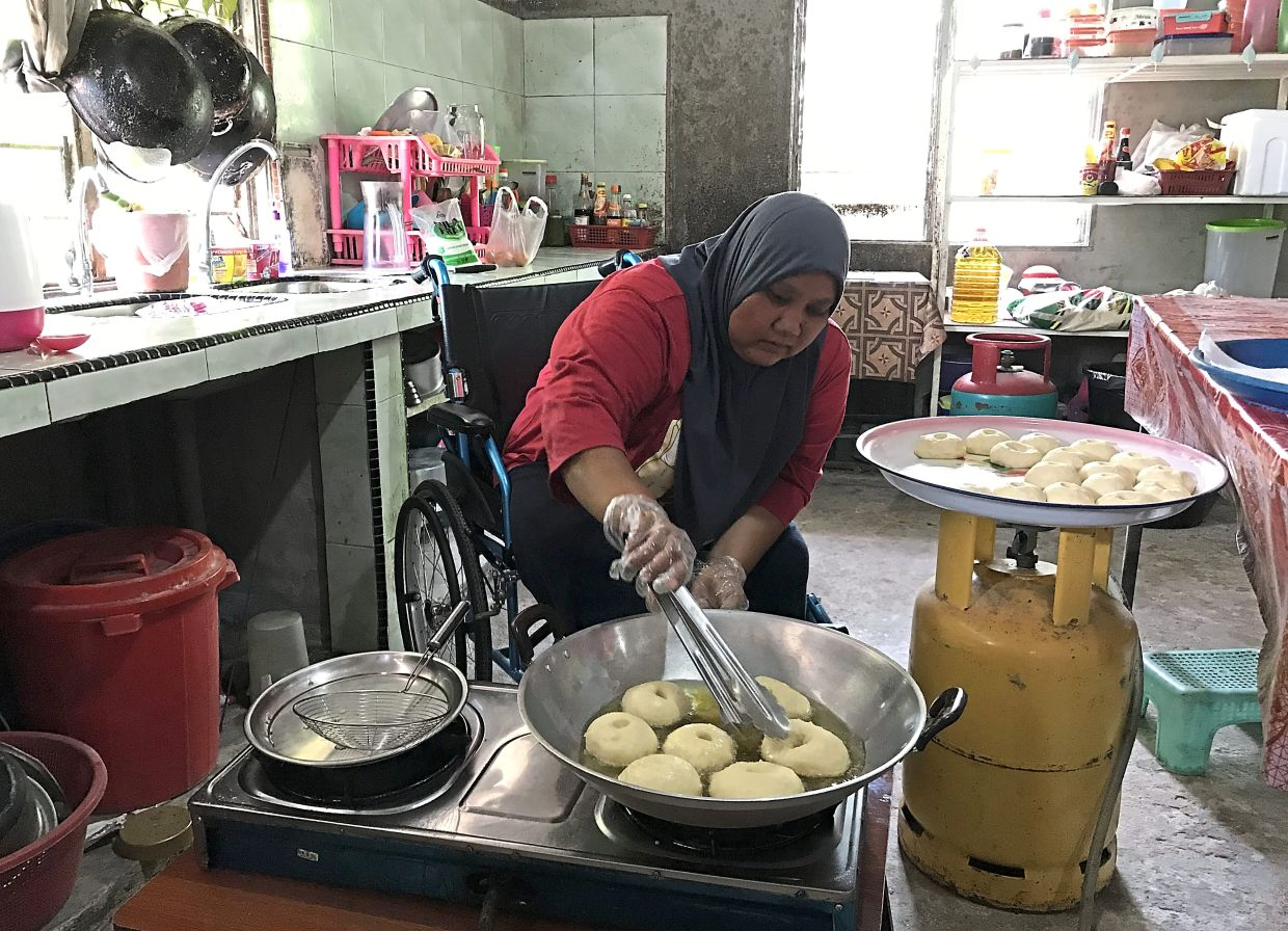 Suriati frying the doughnuts from her wheelchair.