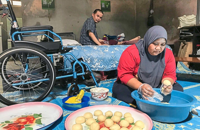 Suriati preparing the dough as her husband Zainal Abidin watches from behind at their home in Kampung Batu Karang, Pasir Mas in Kelantan. — Bernama