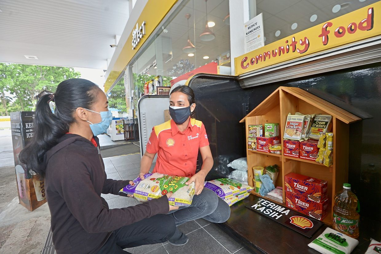 Suraya (right) handing over a bag of rice from a community food box to a member of the public at a petrol station.