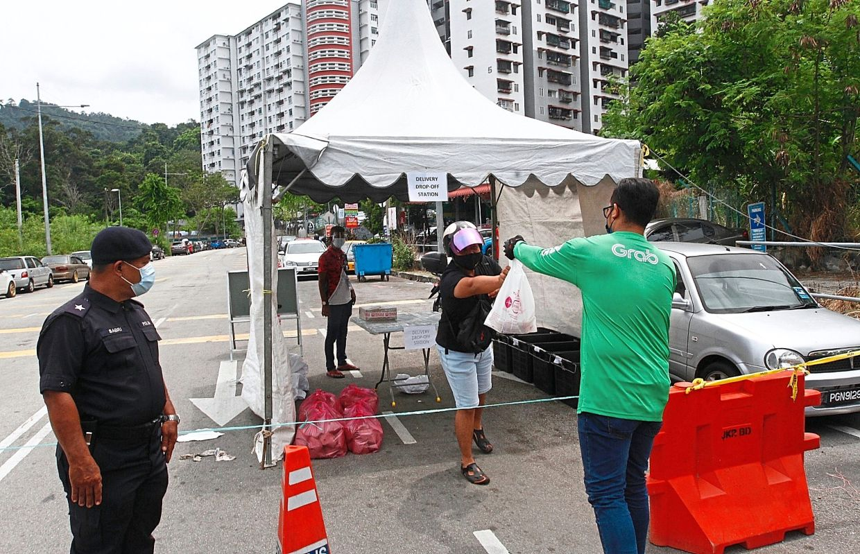 A resident collecting his package from a food deliveryman at the drop-off station at Sri Bayu Apartments.