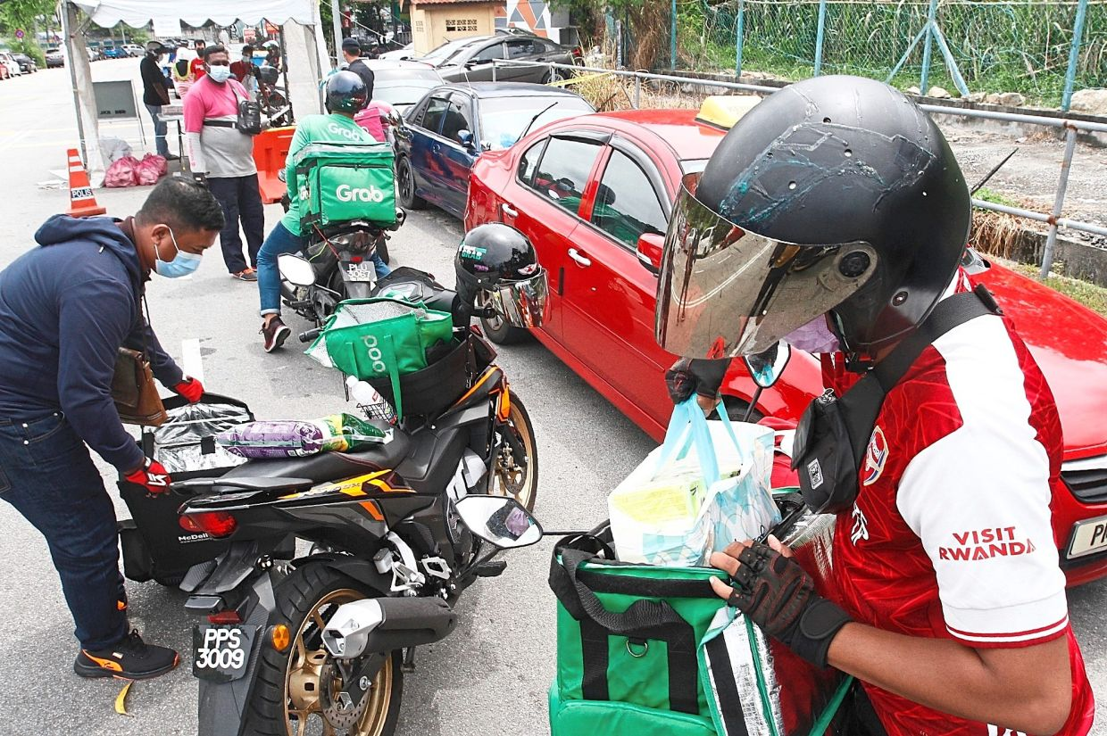 Food delivery workers gathering at a drop-off station in Bayan Lepas to deliver items to customers who are under the enhanced MCO.
