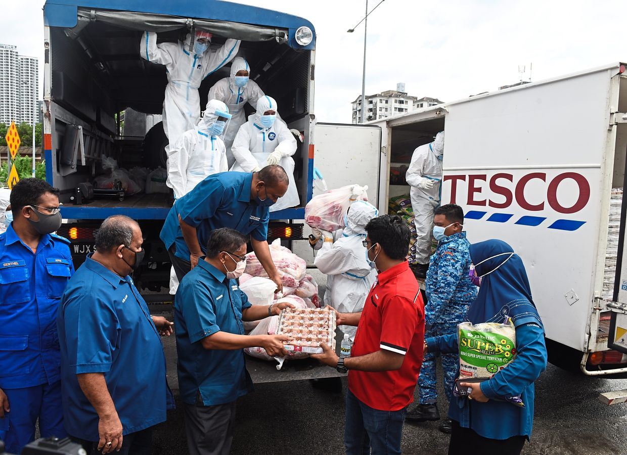 Shabudin (third, left) and state Armada chief Muhammad Shameer Mohamed Sulaiman (in red) preparing to distribute food aid to affected residents in the enhanced MCO zone in Bayan Lepas. — K.T. GOH/The Star