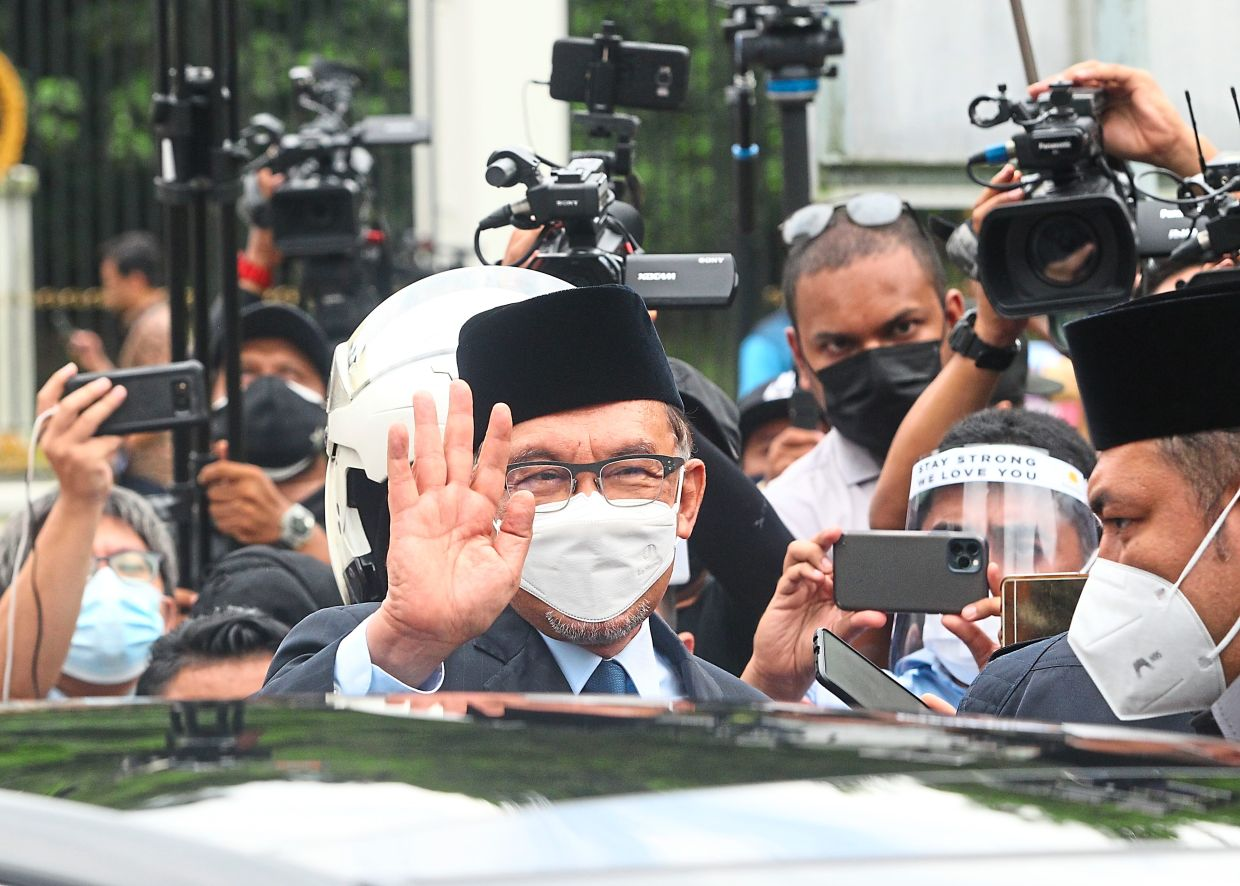 Giving his view: Anwar waving to the media before leaving the palace after his audience with the Yang di-Pertuan Agong. — ART CHEN/The Star