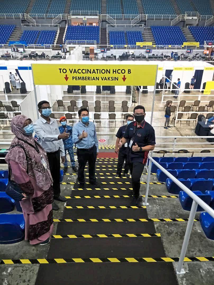 Sim (blue shirt) and Kumaresan (second, left) visiting the vaccination centre at Setia SPICE arena in Bayan Lepas, Penang.
