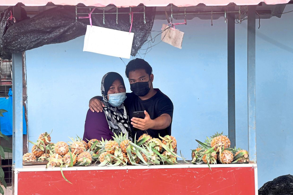 Happy news: Muhammad Arissyafiq Mohamad Arishan hugging his mother Khairul Bariah A. Wahid after checking his SPM results at her pineapple stall near their house in Kuala Nerang, Kedah.