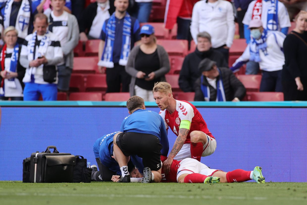 Denmark's Christian Eriksen receives medical attention after collapsing during the match. - REUTERS