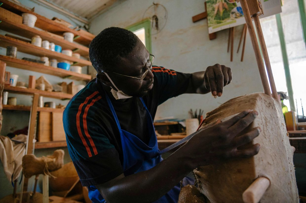 Jean-Paul, a non-monk kora manufacturing worker, takes care of connecting the skin to the ropes of the kora inside the kora making workshop of the Abbey of Keur Moussa, in Senegal. Photo: AFP