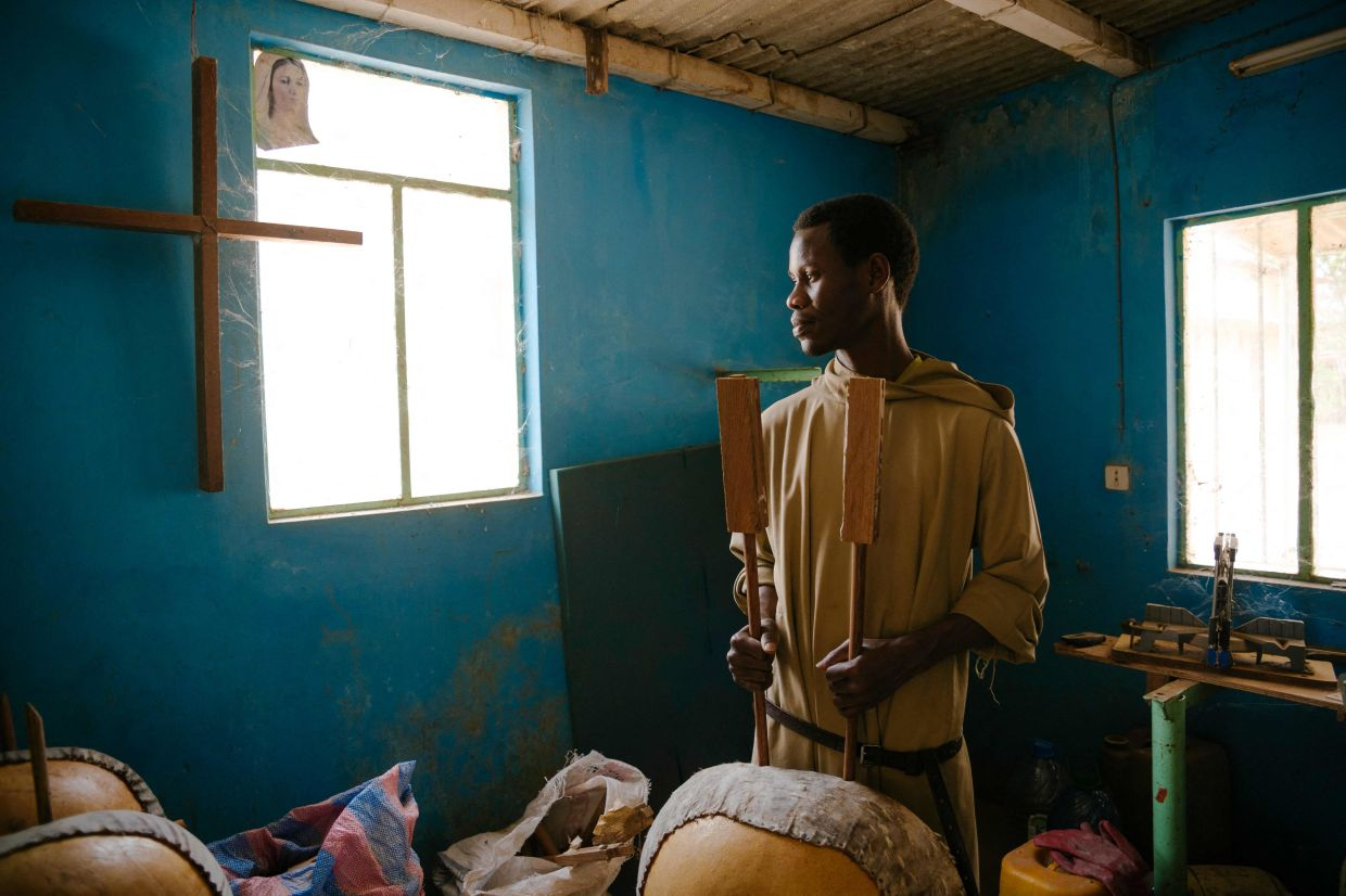 Brother Lazare, the chief of the kora workshop, poses for a portrait inside the kora making workshop of the Abbey of Keur Moussa in Senegal. Photo: AFP