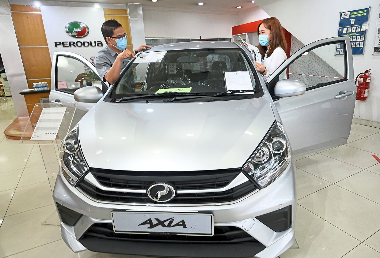 High growth: A sales adviser explains to a potential buyer at a Perodua showroom in Puchong Jaya. As at April 2021, total vehicle sales were up 89% to 199, 556 units from 105, 424 units.