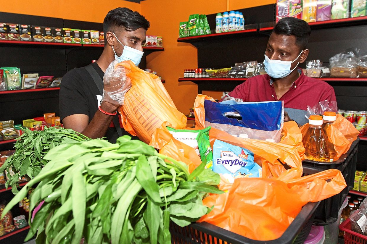 Vicnes (right) and his worker Kesava Raj packing orders for delivery at the Kampong Grocer shop in Taman Palm Grove,Klang.