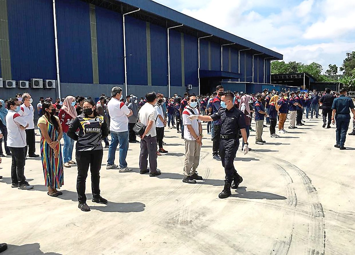 Too large a crowd: Enforcement officers conducting a headcount during the raid at the bicycle spare parts manufacturing factory in Senai.
