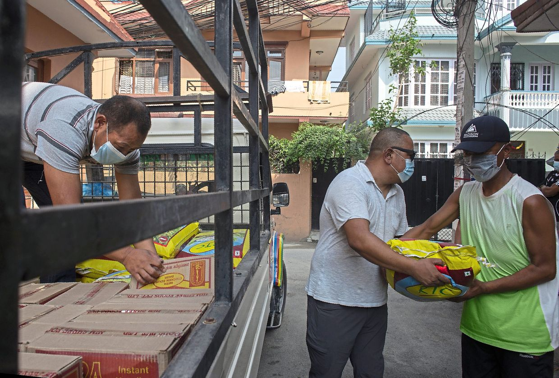 Sherpa (left) distributing food to fellow guides in Kathmandu.
