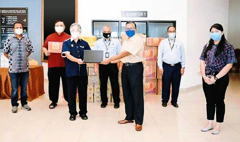 Terengganu Chinese Chamber of Commerce and Industry president Datuk Low Wan Cheong handing over equipment for a vaccination centre to Universiti Sultan Zainal Abidin vice-chancellor Prof Datuk Dr Hassan Basri Awang Mat Dahan.