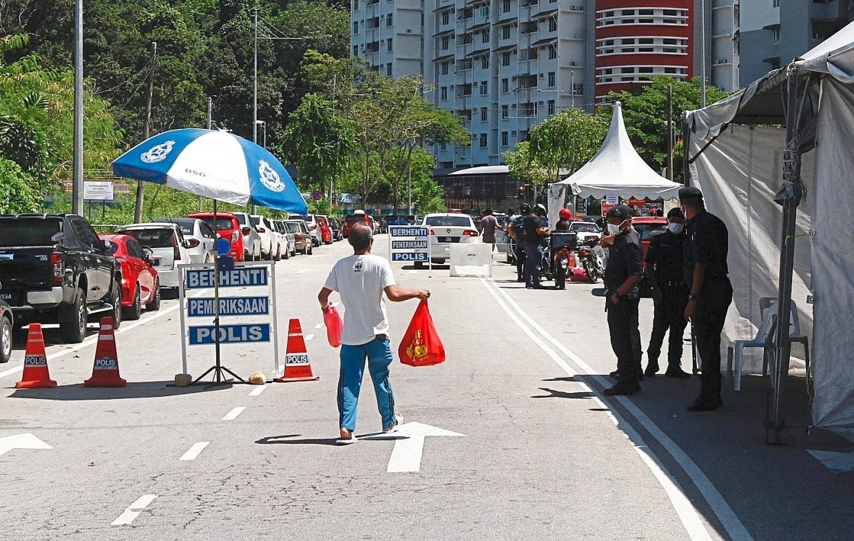 Police personnel manning a roadblock near Sri Bayu Apartment in Bayan Lepas.