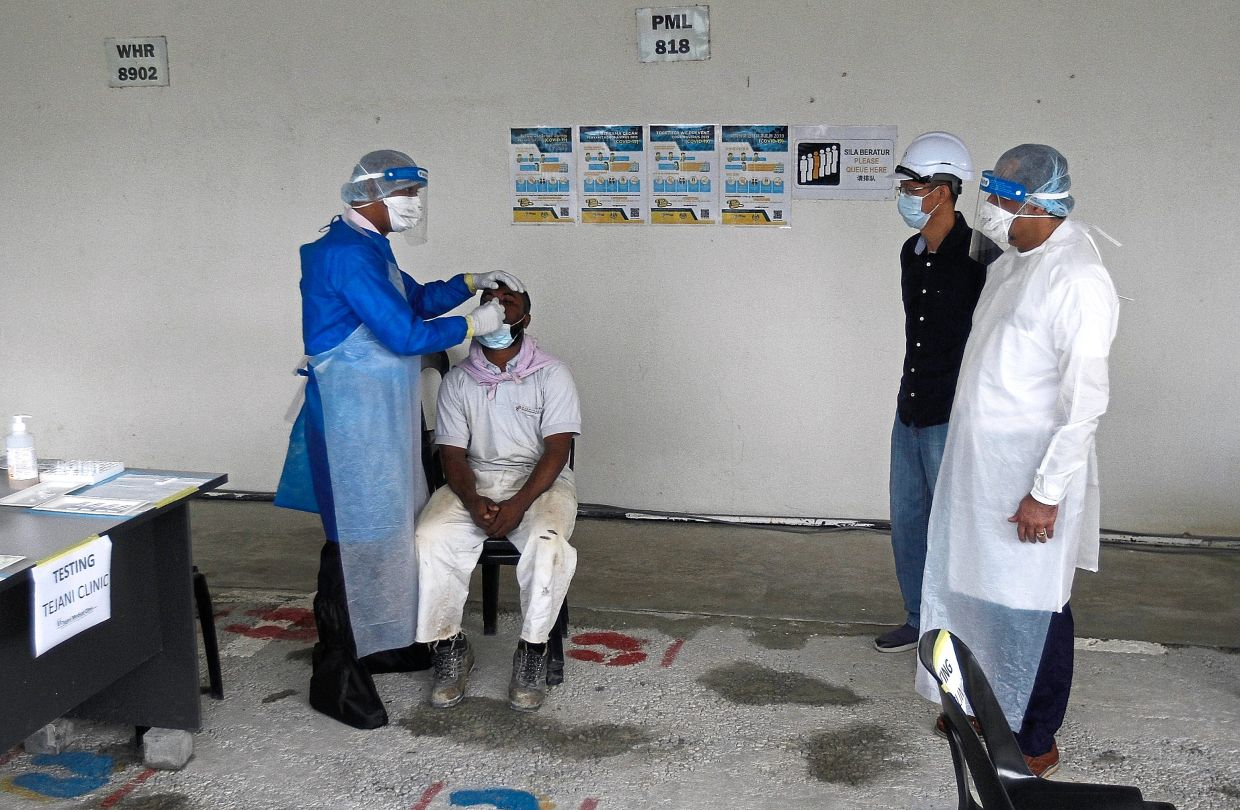 Jagdeep (right) monitoring Covid-19 screening process for foreign workers at a construction site in Penang. — Filepic