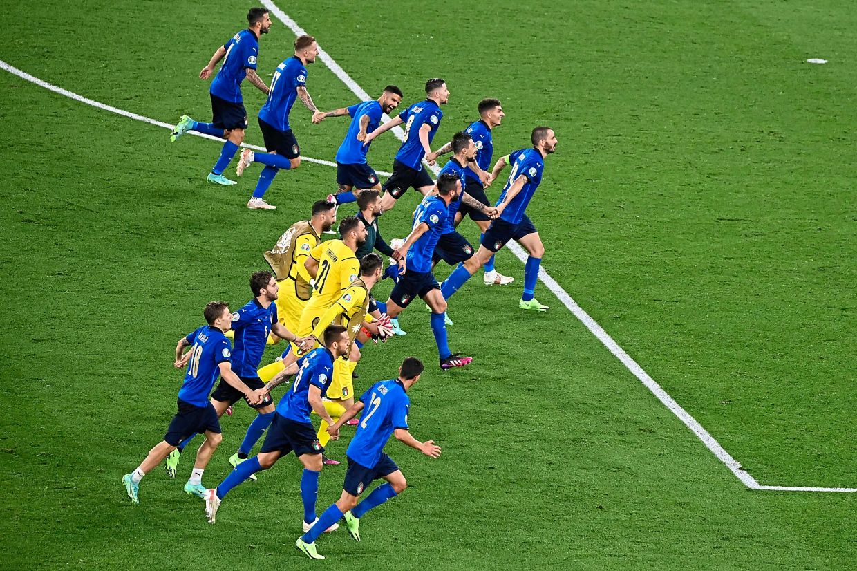 Italy players celebrate their 3-0 win which took them into the last 16. — AFP
