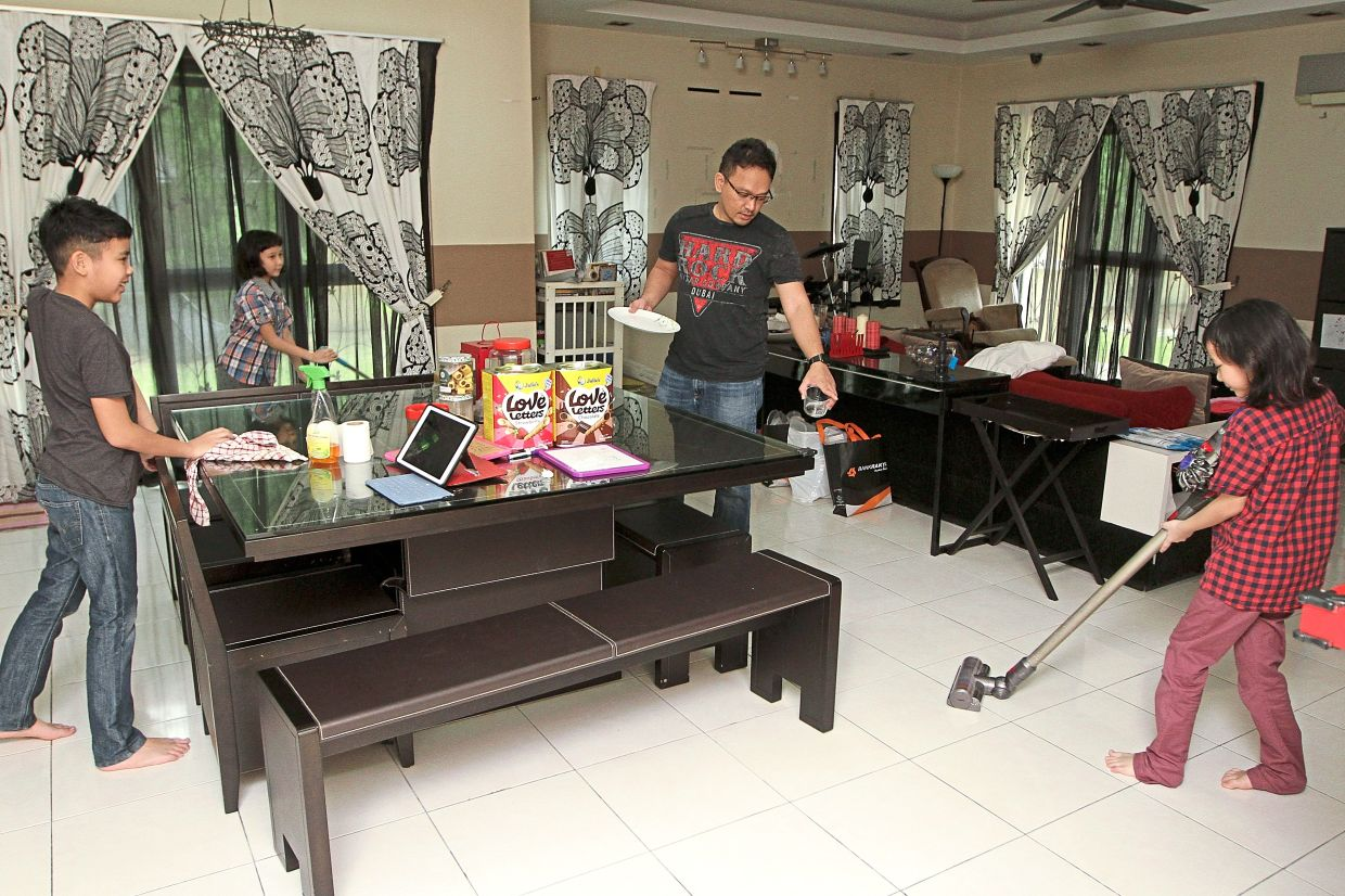 Afif Afham and his children doing chores around the house together. - Photo: YAP CHEE HONG/The Star