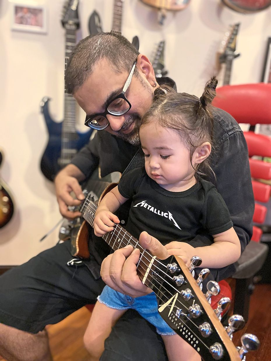 Rithan enjoys spending time with his daughter Liberty as he plays the guitar at home.