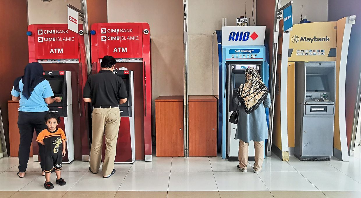 Co-exist: People using ATM machines in Kuala Lumpur. Conventional banks and new digital banks will co-exist as everyone in the ecosystem has an important role to play.