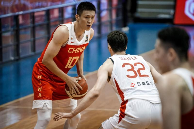 This handout photo taken on Saturday, June 19, 2021, received from the FIBA Asia Cup shows China's Zhou Peng (left) carrying the ball in front of Japan's Avi Schafer during the FIBA Asia Cup basketball qualifier match between China and Japan in Angeles City, north of Manila. - AFP