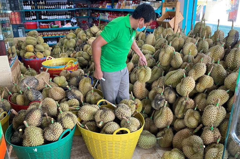 A fruit seller prepares durian for sale at his shop in Phnom Penh. - AFP