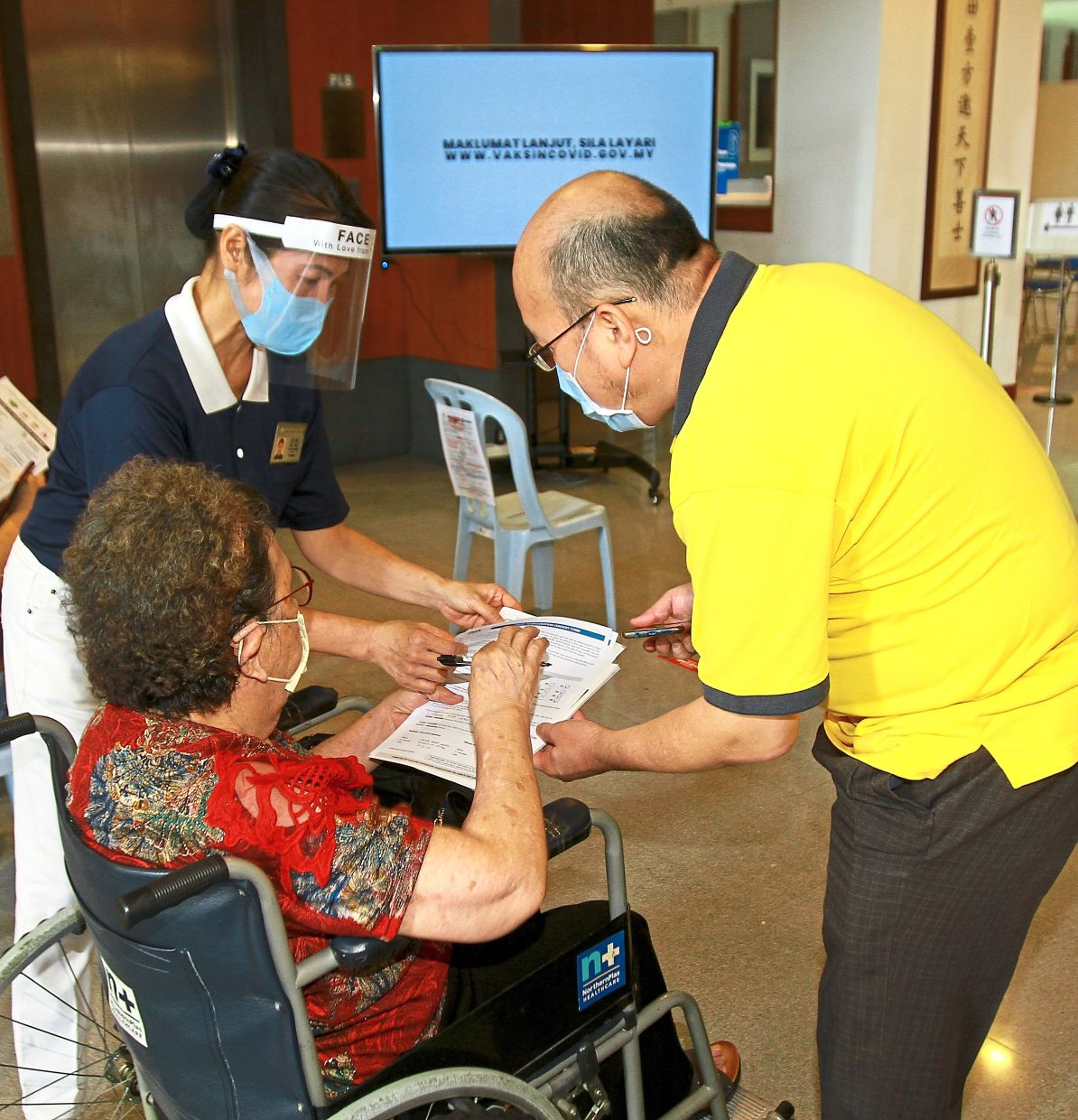 Volunteers stationed at the entrance of the KL Tzu Chi Jing Si Hall to help recipients, who were mostly in their 70s or older.